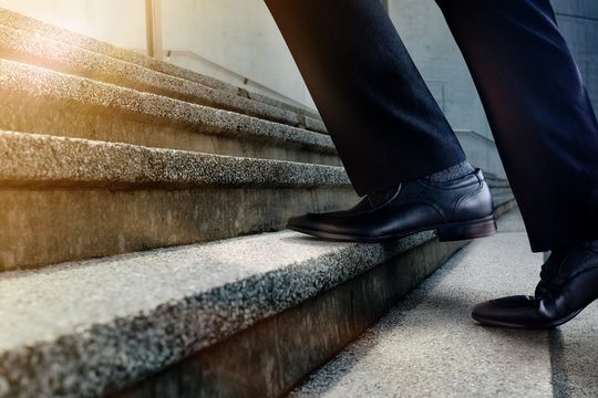 Motivation and challenging Career Concept. Steps Forward into a Success. Low Section of Businessman Walking Up on Staircase. Male in Black Formal Dress