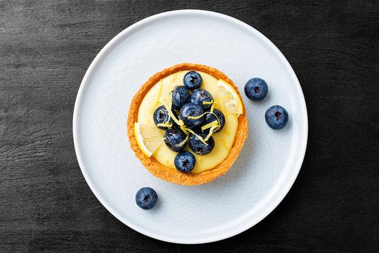 Blueberry tartlet, pie, tart with lemon custard. Black  background.