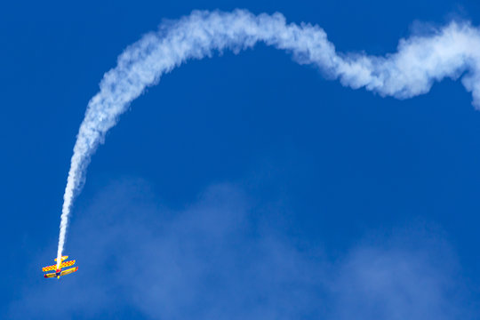 Vintage biplane does stunt with smoke trails in the blue sky.