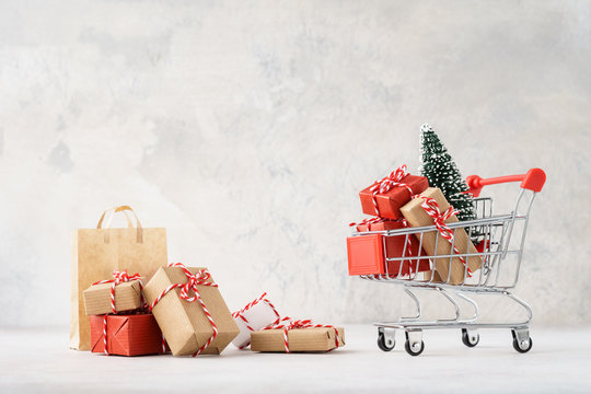 Shopping cart or trolley full of gift boxes and Christmas tree.