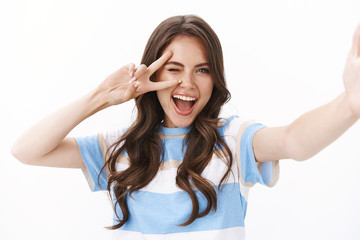 Cheerful enthusiastic woman send girlfriend pics from vacation, summer travel, hold hand camera, taking selfie smartphone, smiling excited show peace victory sign, stand white background