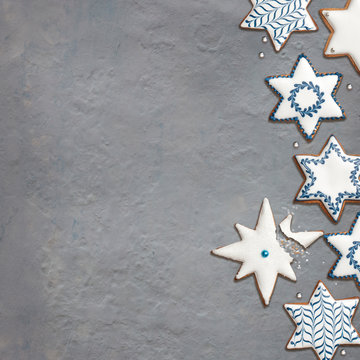 Star shaped artisanal gingerbread cookies for Chanukkah or Christmas party. Empty space for your text.