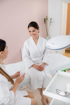 Cheerful young woman talking with beautician at spa salon