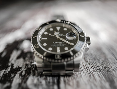 Close-up, shallow focus view of a well-known, Swiss manufactured mechanical diving watch showing detail of the its face, bezel and lettering.