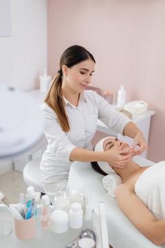 Charming young woman having face massage at beauty salon