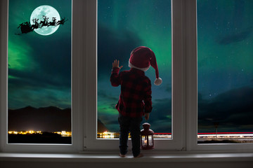 Toddler child standing in front of a big french doors, leaning against it looking out, holding lantern
