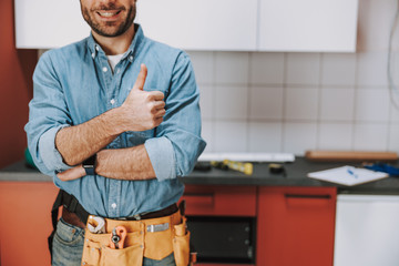 Smiling repairman staying with tool belt at home