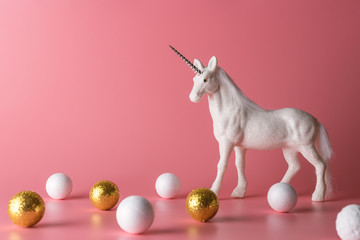Minimal composition with glitter unicorn and white and gold decoration. Magical surreal background.