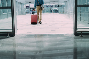 Wall Mural - Man carrying suitcase in terminal stock photo