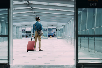 Wall Mural - Young man with baggage leaving airport stock photo
