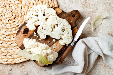 Fototapeta Fresh raw cauliflower sliced into steak on wooden cooking board. Top view, copy space obraz