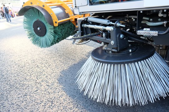 Routine sweeping of municipal streets and highways. Sweeping equipment.Combination of two sweeping brushes of street sweeper close up.