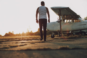 Man going to the plane at sunset Wall mural