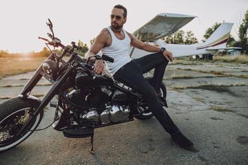 Handsome biker is posing on his motorcycle