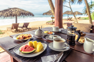 Breakfast on sea beach in Sri Lanka. Table setting with vegan food and coffee in restaurant...