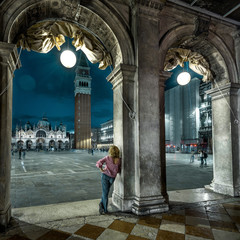 Fototapete - Venice at night, Italy. Young woman is on San Marco square in twilight. Adult girl tourist looks at evening Venice. Vintage architecture of Venice at dusk. Concept of travel and vacation in Venice.