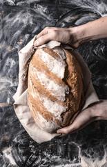 Trzymanie bochenka chleba w dłoniach na czarnym tle w stylu rustykalnym