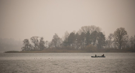 Fishermen are seen in a boat on a lake during a foggy autumn day on the outskirts of Minsk