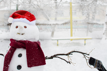 snowman in Santa hat and scarf outdoors