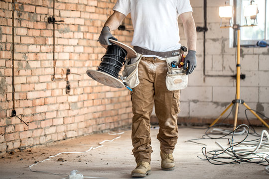 Electrician with tools, working on a construction site. Repair and handyman concept.