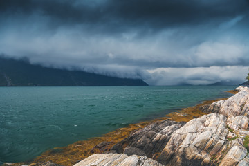 Wall Mural - Dramatic dark thunderclouds over mountains and fjord in norway, travel to scandinavia. The beauty of northern nature