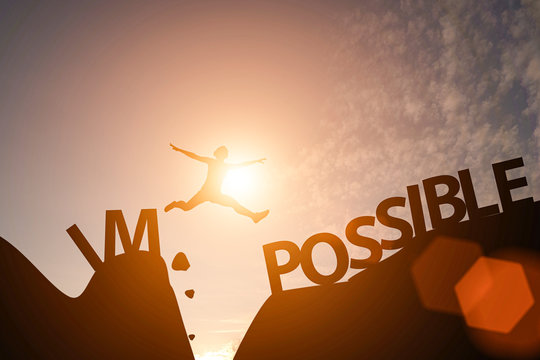 Man jump between impossible wording and possible wording on mountain. Mindset for career growth business.