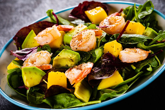 Salad with shrimps on black stone plate