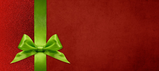 Fotomurales - gift card wishes merry christmas background with green ribbon bow on red shiny vibrant color texture template with blank copy space