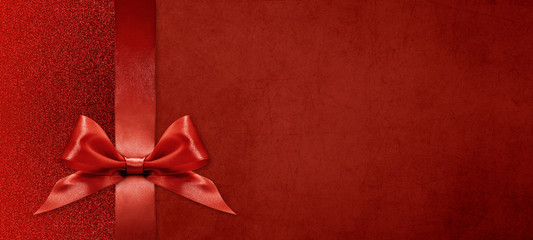 gift card wishes merry christmas background with red ribbon bow on red shiny vibrant color texture...