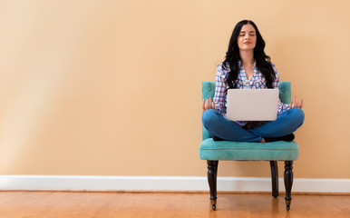 Young woman with laptop in a meditation pose pose sitting in a chair