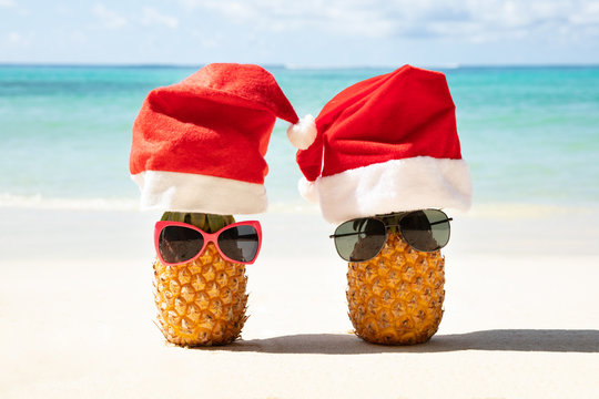 Santa Hats And Sunglasses On Two Pineapples At Beach