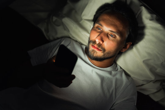 Young handsome and tired man with a beard cannot sleep and is watching something on his phone at night.