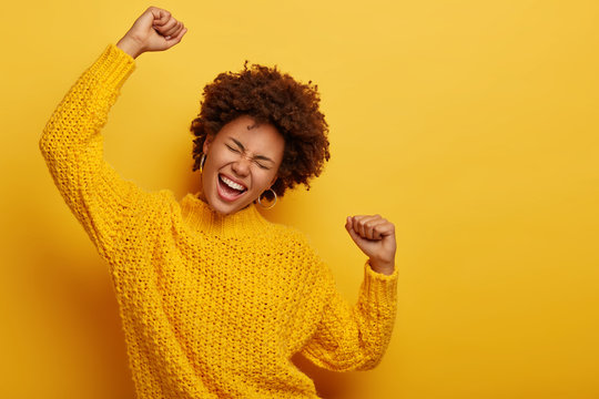 Curly haired girl in winter yellow sweater dances with arms spreading in air, enjoys music, has overjoyed face expression, being on party, enjoys concert poses indoor. People, fun, emotions, happiness