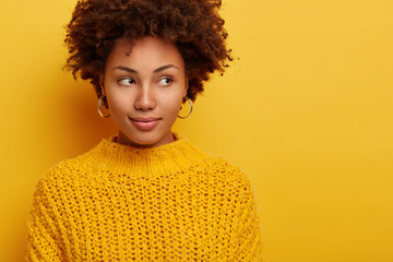 Portrait of attractive brunette woman peeks aside, has serious face expression, stands alluring against yellow background, wears no makeup, dressed in warm sweater, thinks deeply about something