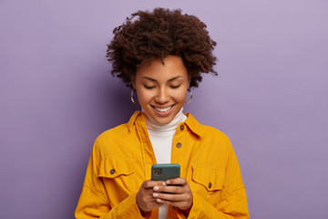 Photo of glad female blogger types text content for web publication, focused in smartphone, wears yellow shirt, checks received notification, smiles gently, isolated over purple studio wall.