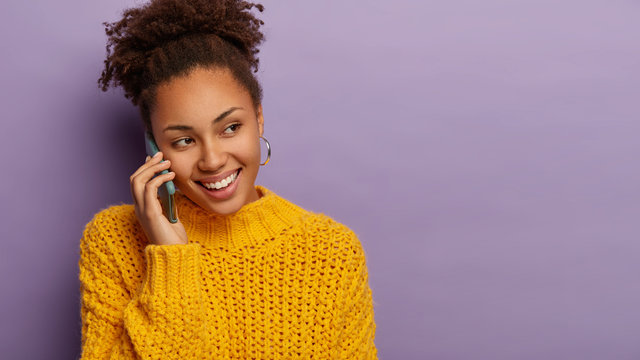 Smiling hipster girl with happy expression uses mobile application for making conversation, feels good during communication, looks away wears knitted sweater poses on violet wall blank space for promo