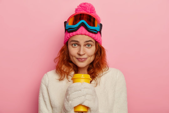 Girl snowboarder wears warm winter outfit, white mittens, holds takeaway coffee, has sporty lifestyle, rests after skiing in mountains, enjoys traveling during holidays, isolated over pink background