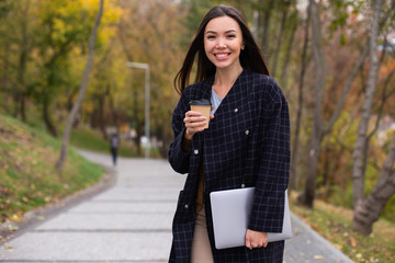 Young beautiful smiling woman in coat with coffee to go and laptop joyfully looking in camera in...