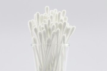 Many cotton swabs in the glass on white background