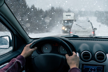 A man drives a car on a winter road in a blizzard