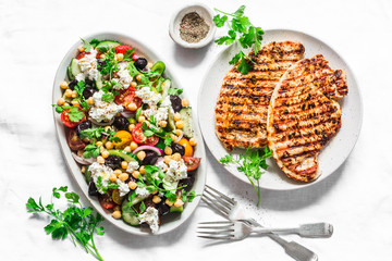 Mediterranean style lunch table - Greek chickpeas salad and pork chops on light background, top view