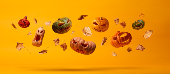 Several flying scary halloween pumpkins and dry leaves