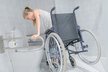 Woman moving from wheelchair to bathroom