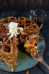 cut pumpkin waffles with pecans topped with butter and syrup with bite on fork