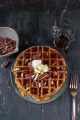 pumpkin waffles with pecans topped with butter and syrup flat lay