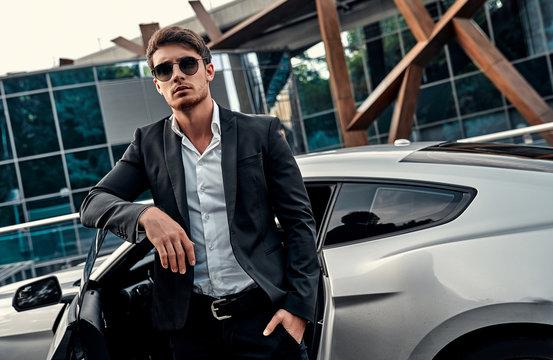 Handsome businessman near car