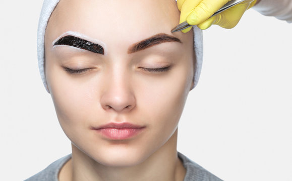 Make-up artist plucks eyebrows to a beautiful woman in a beauty salon. Professional skin care, plucking eyebrows and permanent makeup.