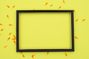 Photo frame on a yellow background with orange flower petals. Free space for an inscription.