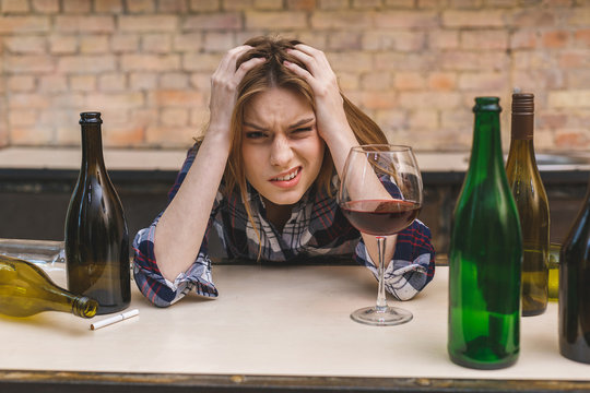 Young sad and wasted alcoholic woman sitting at kitchen couch drinking red wine, completely drunk looking depressed lonely and suffering hangover in alcoholism and alcohol abuse.
