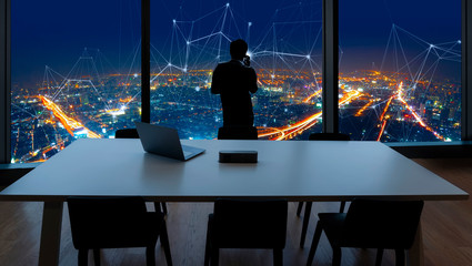 Wall Mural - Businessman standing using smart phone and Business Wireless network in office desk and windows and Bangkok city view.